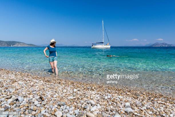 Woman standing in sea looking over her shoulder at couple swimming, Ithaki, Greece