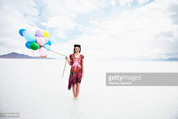 Woman standing in shallow water holding balloons