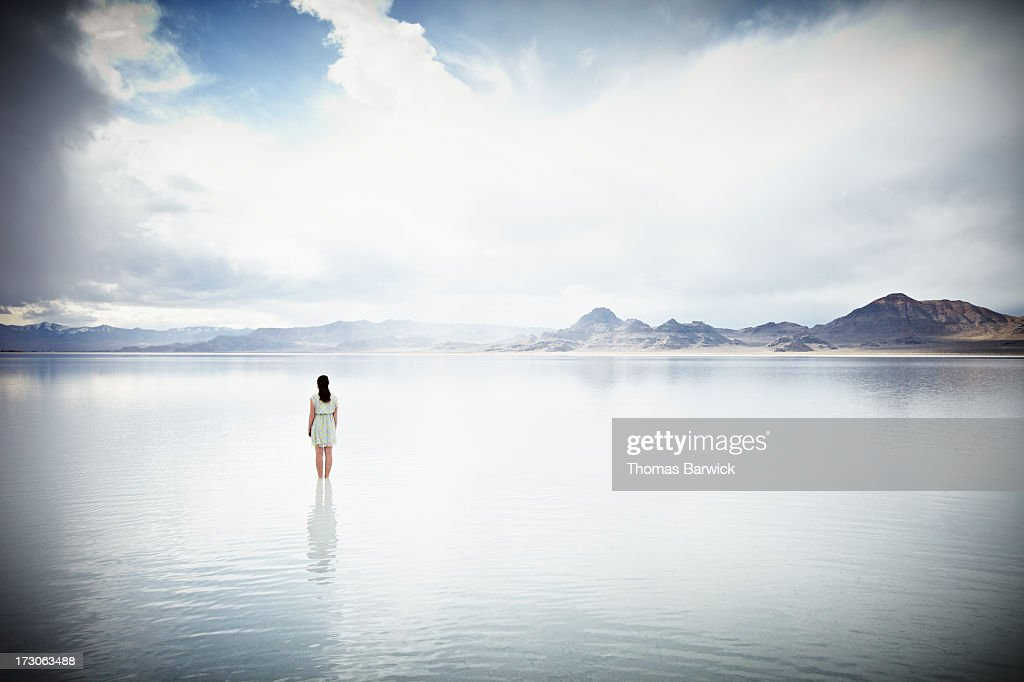 Woman standing in shallow water looking out : Stock Photo