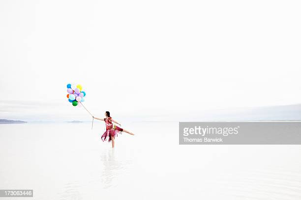 Woman standing in shallow water with balloons