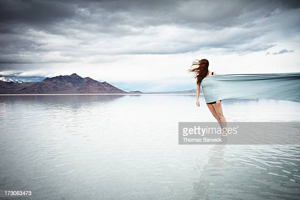 Woman standing in shallow water wrapped in fabric