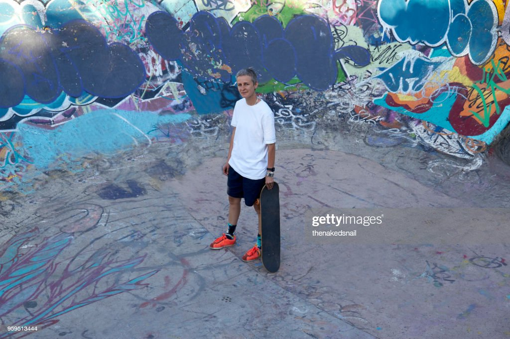 Woman standing in skate park with skateboard : Stock-Foto