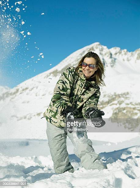 Woman standing in snow, laughing at snowball bursting in air