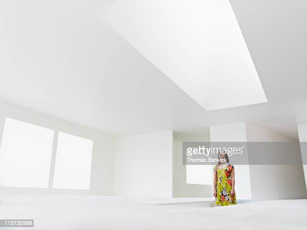 Woman standing in stairwell looking up at skylight