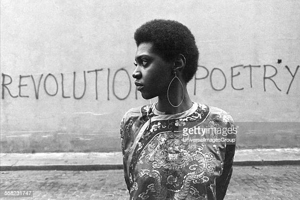 Woman standing in street by a wall painted with 'Revolution poetry' London UK 1960's