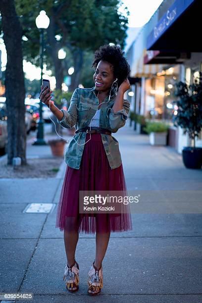 Woman standing in street, holding smartphone, wearing earphones, smiling
