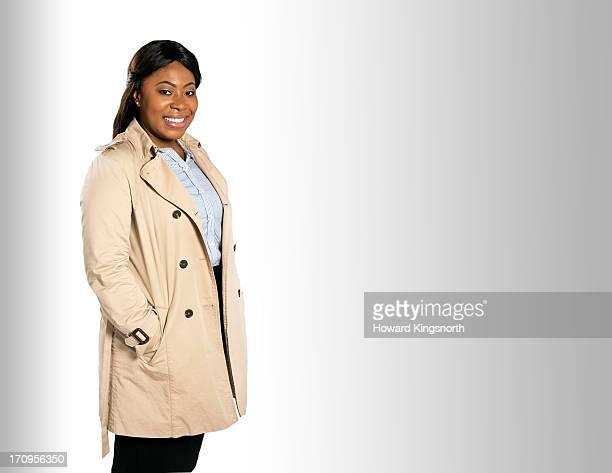 woman standing in street looking to camera - トレンチコート ストックフォトと画像