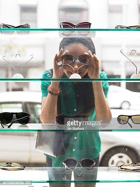 Woman standing in street, peering at window display of eyeglasses, view from inside shop