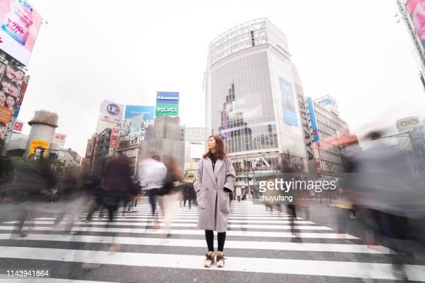 vrouw staande in de straat, shibuya - kruispunt stockfoto's en -beelden
