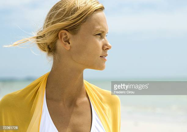woman standing in sun on beach, looking to distance - squinting stock photos and pictures
