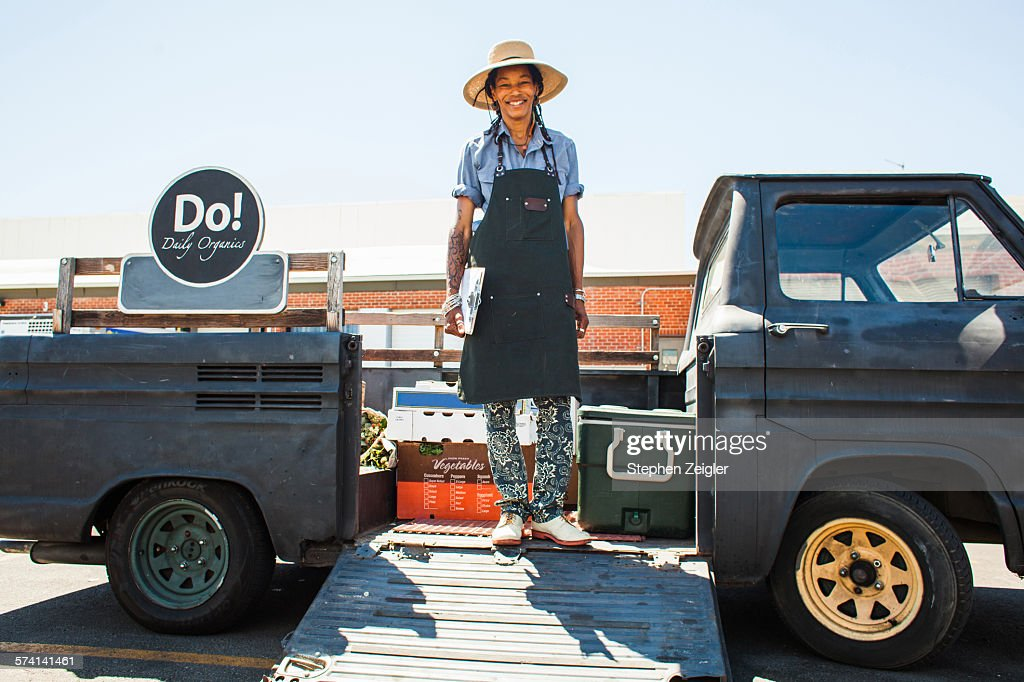 50-something mixed race woman wearing a wide brimmed hat and apron standing in the back of her vintage truck filled with organic produce looking at the camera and smiling