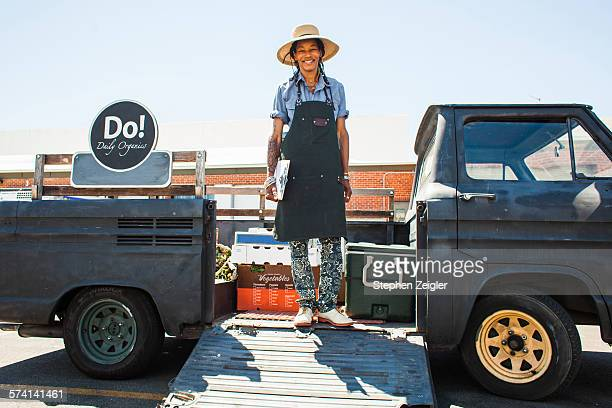 Woman standing in the back of her vintage truck