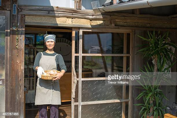A woman standing in the door of a bakery