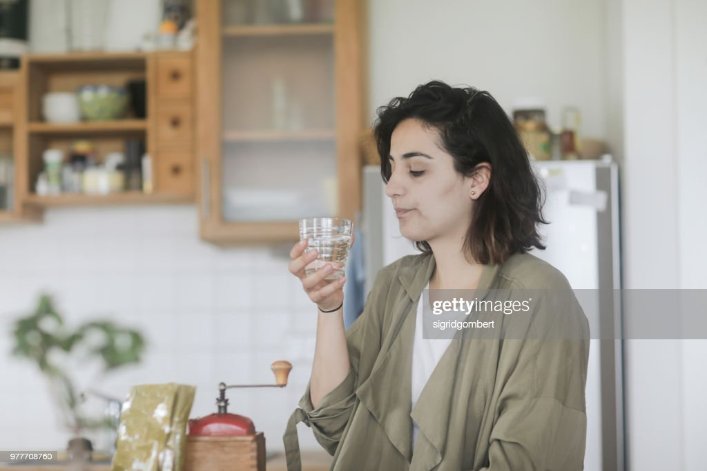 Woman standing in the kitchen drinking a glass of water : Stock Photo
