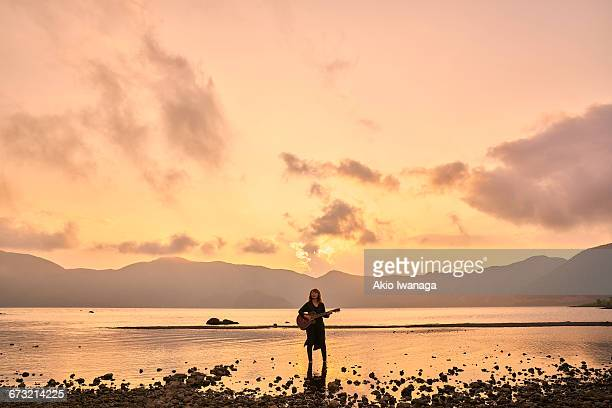 woman standing in the lake of the sunset - akio iwanaga ストックフォトと画像
