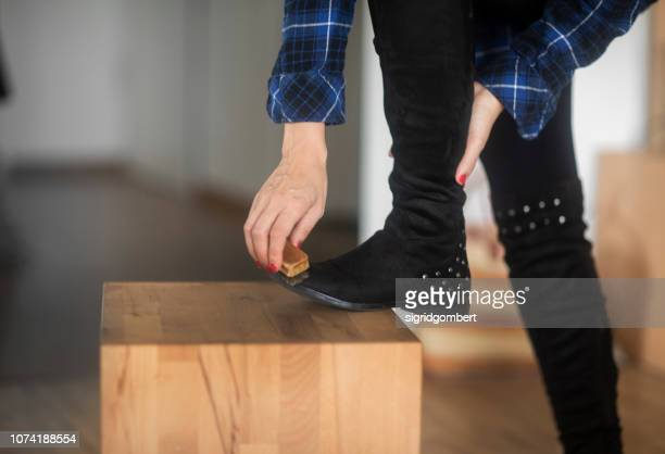 woman standing in the living room cleaning her boots - suede stock pictures, royalty-free photos & images