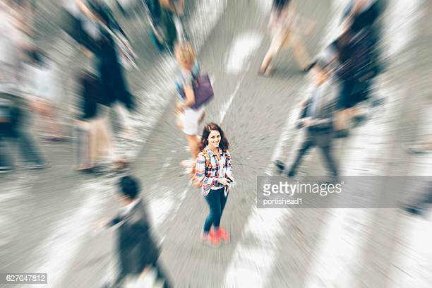Woman standing in the middle of crowd crossing street