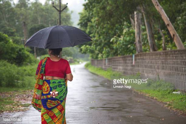 woman standing in the rain under her umbrella - monsoon stock pictures, royalty-free photos & images