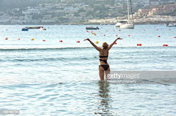 woman standing in the sea with her arms raised at sunrise, melieha, malta - maltese islands stock photos and pictures