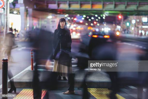 woman standing in the street at night in tokyo - affollato foto e immagini stock