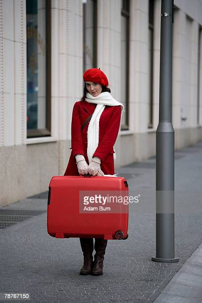 A woman standing in the street with a suitcase
