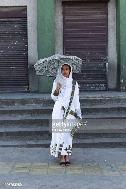 Woman standing in the street with an umbrella