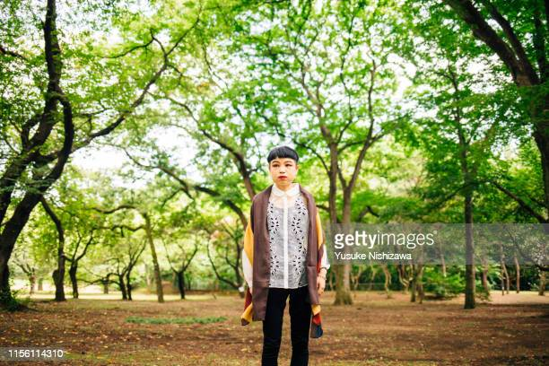 woman standing in the woods - yusuke nishizawa stock pictures, royalty-free photos & images