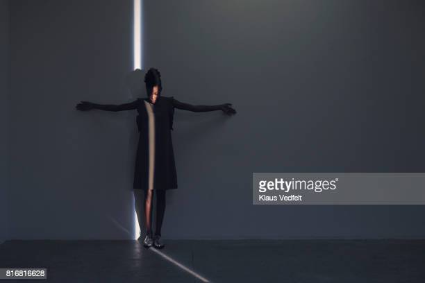 Woman standing in thin light stripe, in studio with concrete floor