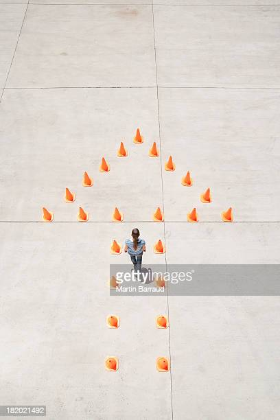 Woman standing in traffic cones forming arrow