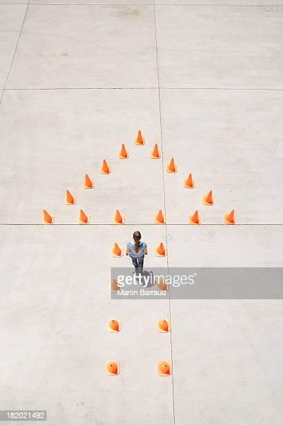Mulher de pé em cones de trânsito, formando a seta