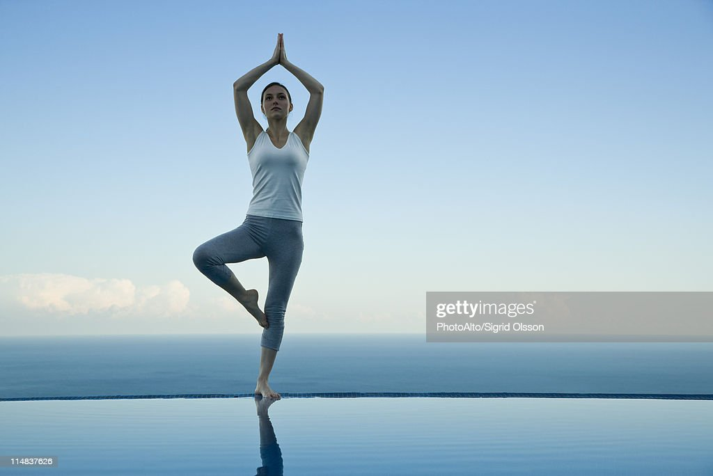 Woman standing in tree pose on edge of infinity pool : ã¹ããã¯ãã©ã