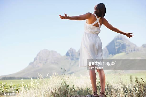 femme debout dans la vallée, avec les bras écartés - les bras écartés photos et images de collection