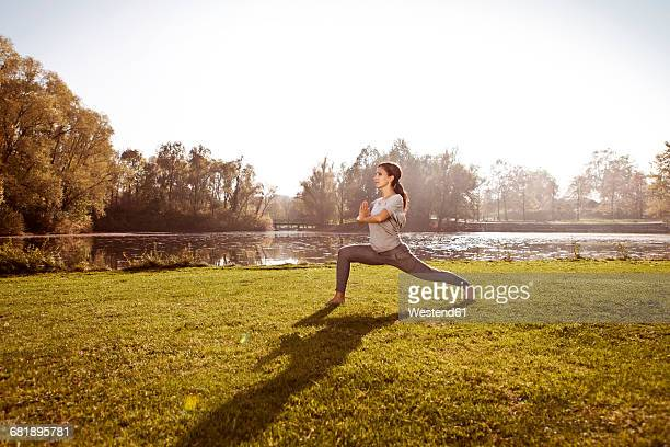 Woman standing in Virabhadrasana position at lakeside