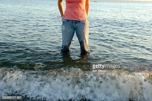 woman standing in water at beach, hands on hips, low section - wet jeans stock photos and pictures