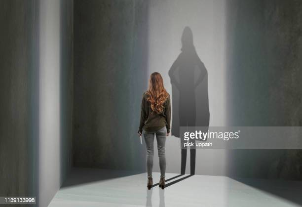 woman standing in with superhero shadow - ombra in primo piano foto e immagini stock