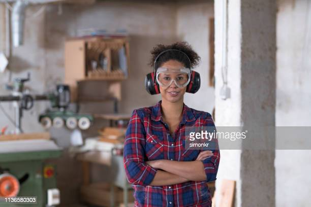 woman standing in workshop - rolled up sleeves stock pictures, royalty-free photos & images