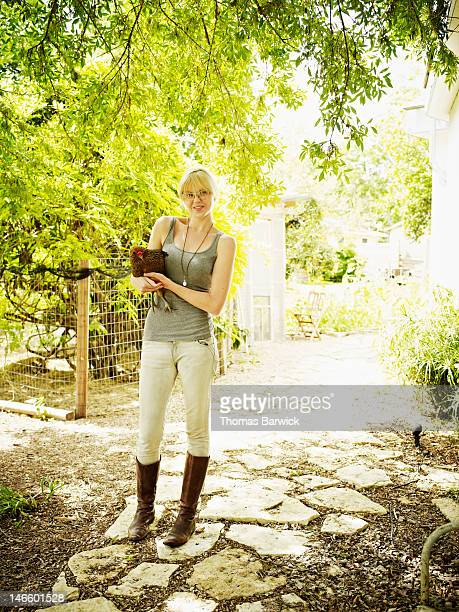 Woman standing in yard holding pet hen smiling