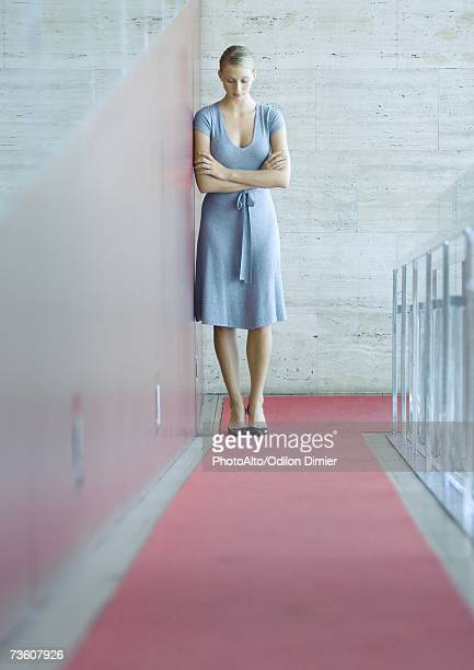 Woman standing, leaning against wall, head down, full length portrait