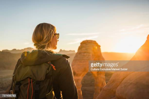 Woman standing, looking at Delicate arch, rear view, Arches national Park, Moab, Utah, USA