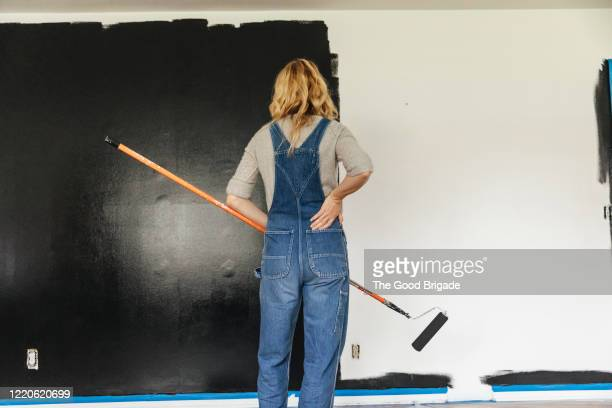 woman standing looking at painted wall at home - bib overalls stock pictures, royalty-free photos & images