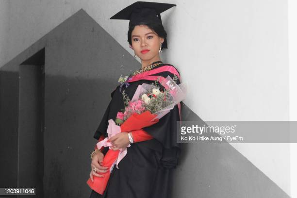 woman standing looking away while standing with bouquet against wall - ko ko htike aung stock pictures, royalty-free photos & images