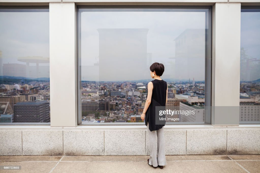 A woman standing looking over a city from a high viewing point. : ストックフォト