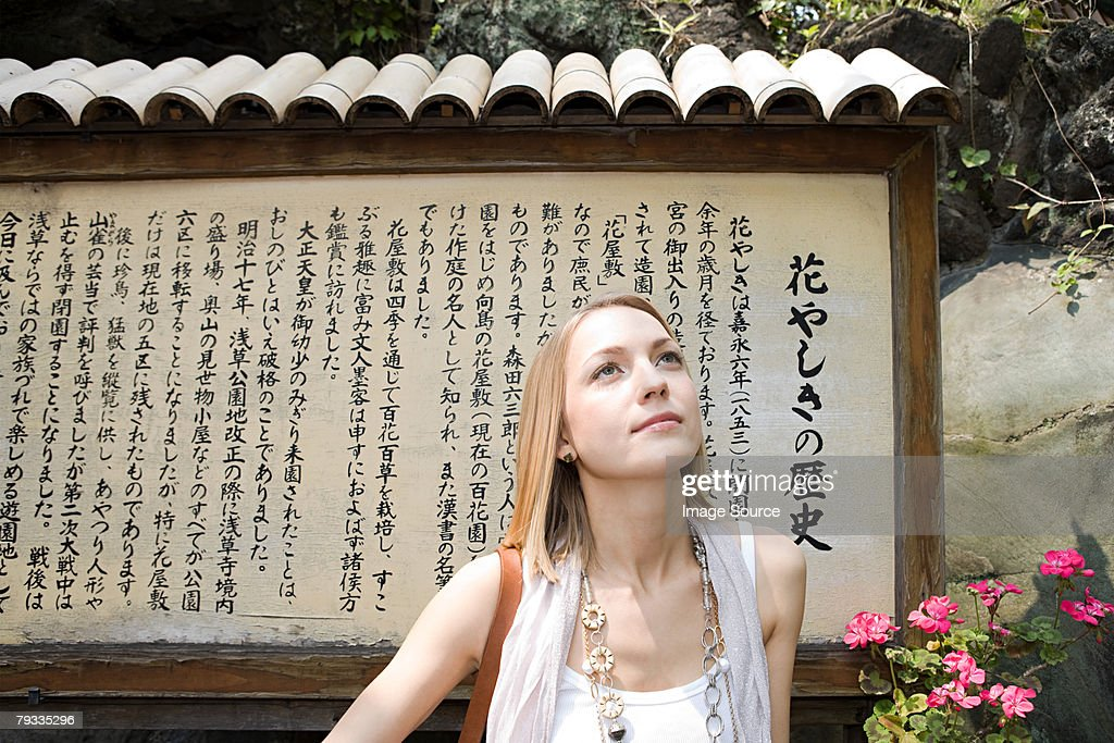 Woman standing near a japanese sign : Stock Photo