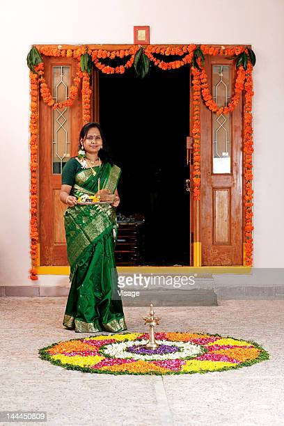 Woman standing near a pookalam