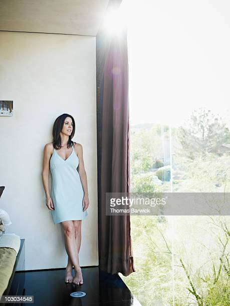 Woman standing near bedroom window looking out