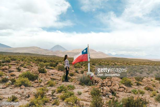 donna in piedi vicino alla bandiera cilena nel deserto di atacama in cile - bandiera del cile foto e immagini stock
