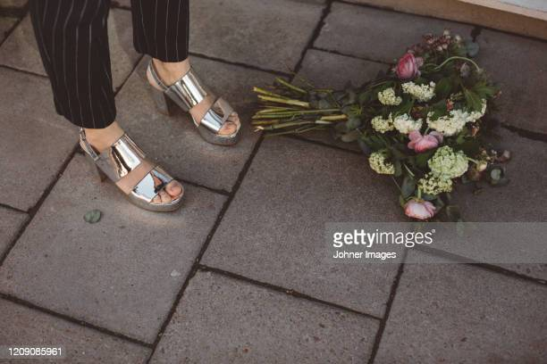 woman standing near flower bouquet, low section - low section stock pictures, royalty-free photos & images