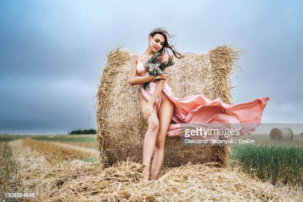 woman standing near hay bales in field against sky - satin dress stock pictures, royalty-free photos & images