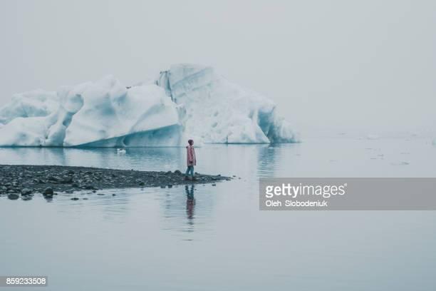 frau, die in der nähe von jökulsárlón lagune - iceberg stock-fotos und bilder