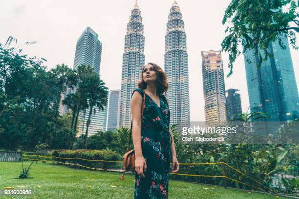 woman standing near    petronas tower - kuala lumpur stock pictures, royalty-free photos & images